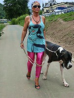 Sexy mature wearing pink leggings is walking with her dog